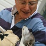 Senior citizen holds an Italian Greyhound, who looks at him lovingly.