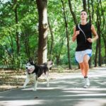 man runs with dog. forced exercise can injure dog