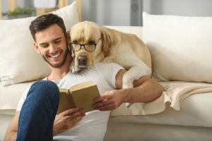 Millennial man reads to dog. Millennial increasingly choosing dogs over kids.