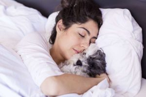 Science says sleep with your dog. Sleeping woman cuddles with her Cavapoo.