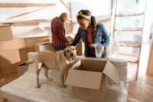 Moving with your dog: African American couple unpacks boxes at their new home as yellow Labrador retriever watches.