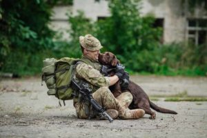Soldier hugs military dog. Unconventional adoptions include military and police dogs as well as older dogs or dogs with serious medical conditions who are otherwise hard to place.