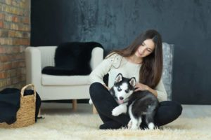 Woman snuggles with her husky puppy. Create a dog-friendly home.