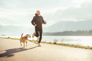 Man runs with his beagle. Use dog-friendly exercises to get fit with your dog.