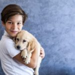 Teen boy cuddles with golden retriever puppy. Studies show that attachment to pets declines during the teen years.
