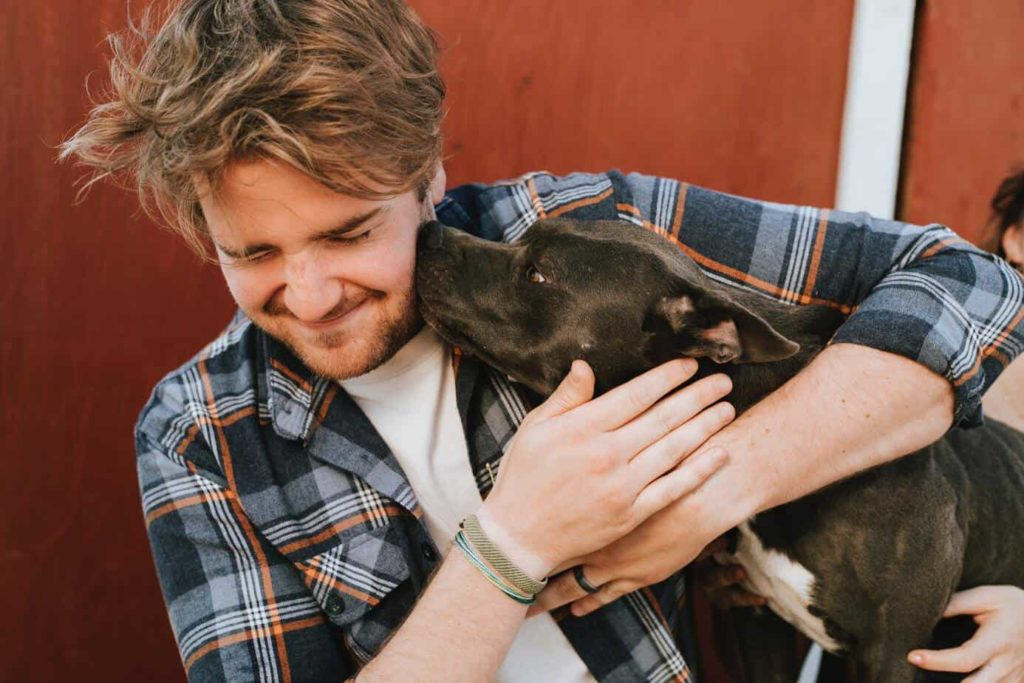 Puppy gives man a kiss. If you have an ESA, know that there are emotional support animal regulations to protect your need for your pet, if you follow the rules.