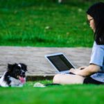 Student studies while small dog lounges on the grass. Before you take your dog to college, consider whether you'll have the time and financial resources to give your dog proper care.