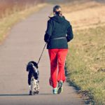 Woman jogs with her dog. Always consult with your vet before adding easy exercises with your dog.
