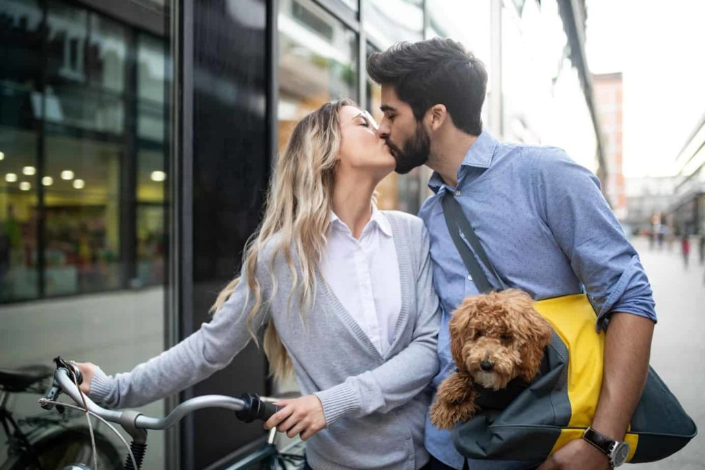 Couple kisses on a busy street while carrying a goldendoodle puppy. Dogs improve relationships by making you more loving and that feeling rubs off on anyone you spend time with, especially your partner.