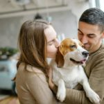 Couple hugs while holding a beagle puppy. Dogs improve relationships. Interacting with your dog increases your levels of oxytocin and dopamine and that promotes positive emotions and encourages bonding.