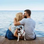 Man and woman kiss on a dock while a French Bulldog sits between them. Follow five rules to become closer to your partner's dog and your partner. If you treat her dog well she will know that you will treat her well.