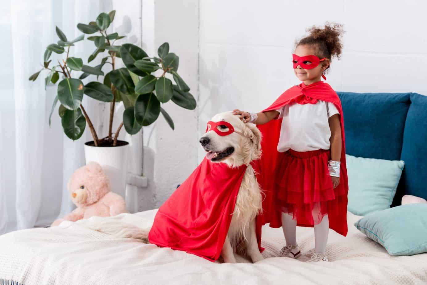 Little girl and her golden retriever dress like super heroes. Dogs teach kids valuable life lessons including responsibility, socialization, love, and friendship, and the importance of exercise.