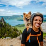 Woman hikes with Pomeranian in her backpack. Include your dog in your eco-friendly life by buying natural dog food and biodegradable poop bags.