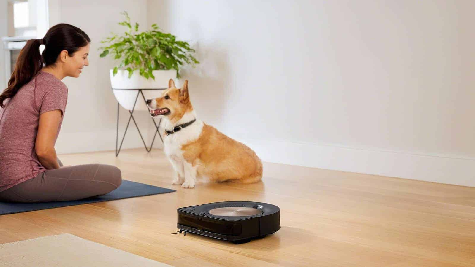 Woman talks to corgi while robotic vacuum cleans the floor.