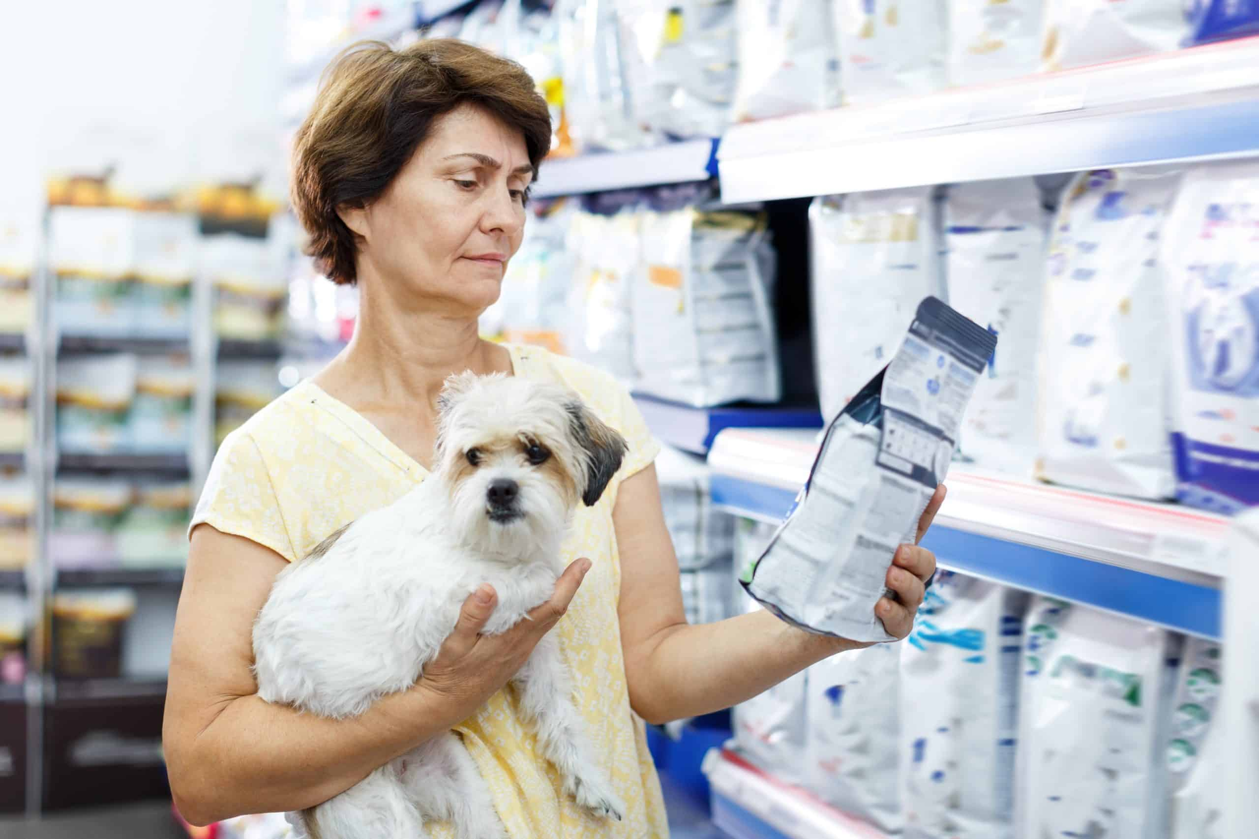 Woman reads information on dog food bag. How to choose dog food: Start by considering your dog's breed, size, and activity level. Then read the ingredients and research the company.
