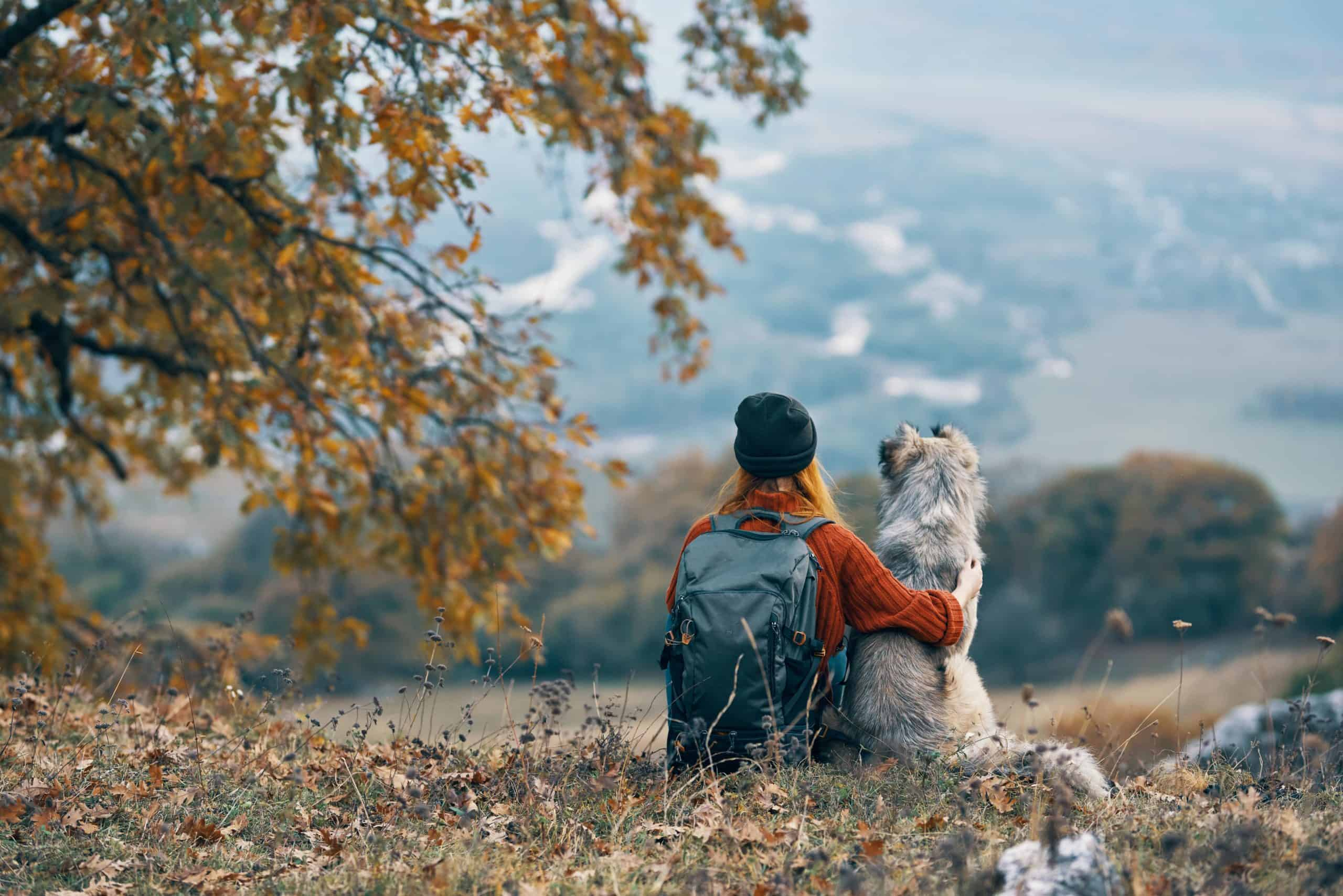 Woman on mountain hike cuddles with her dog. Bringing your fur babies on an adventure requires you to keep them safe and bring all of the adventure essentials required.