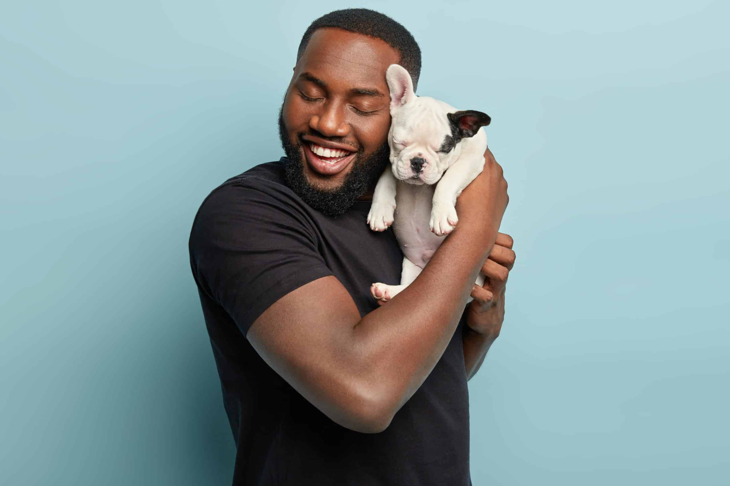 Man cuddles with a French bulldog puppy. Adopting a dog during quarantine has clear advantages, but consider your time, housing, and finances before making a decision.