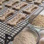 Homemade dog treats cool on racks after baking.