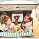 Hipster couple camps with their dog in vintage van. Use this list of tips and tricks to make car camping with your dog go smoothly.