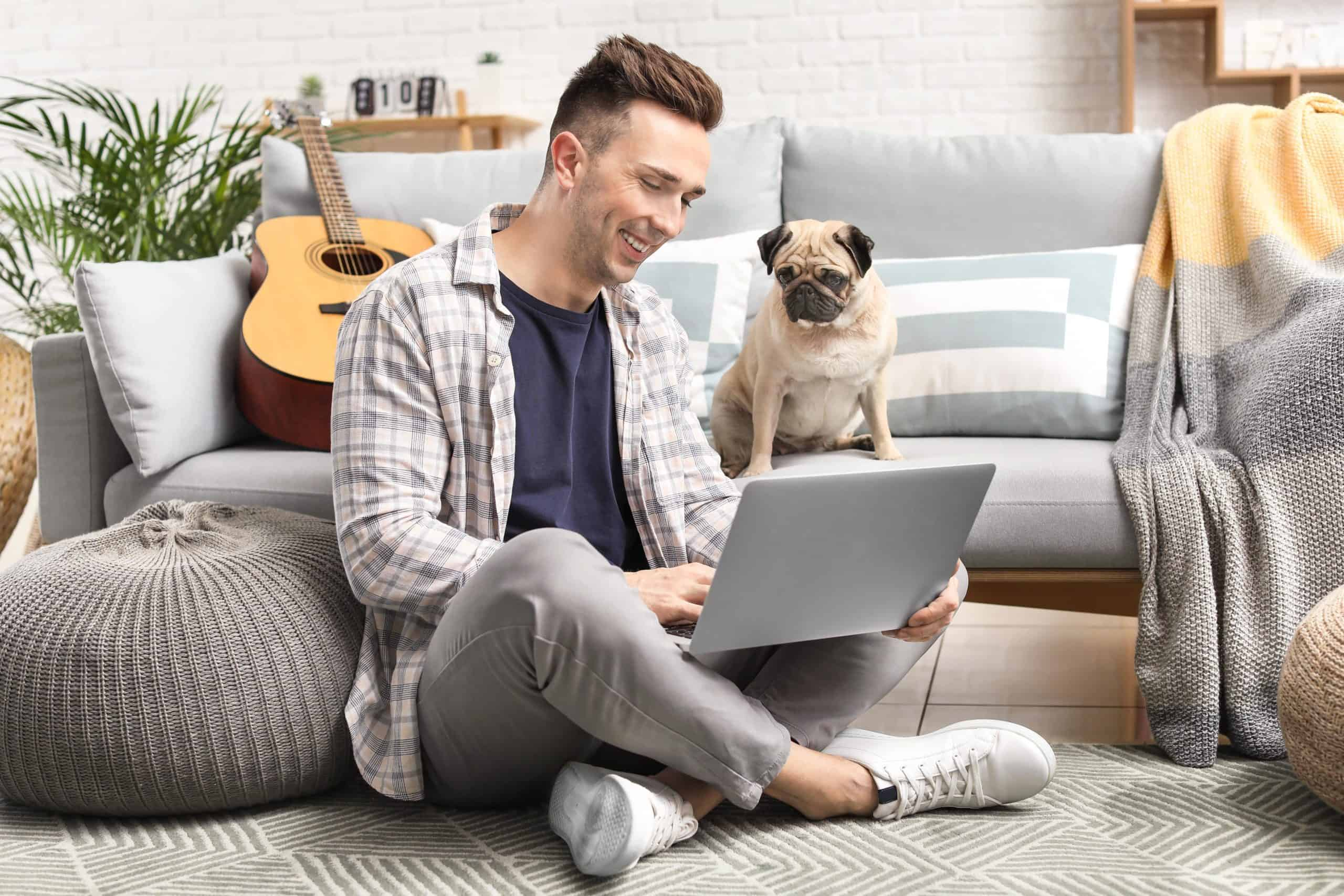 Man sits on floor while typing on his laptop as a Pug looks on. Having a dog helps you become more perceptive.