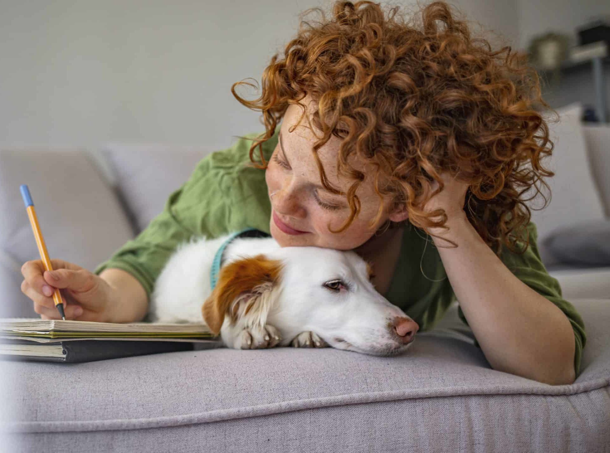 Woman cuddles with dog while studying. Bring your pet to college to help you manage your homesickness and the stress of college life.