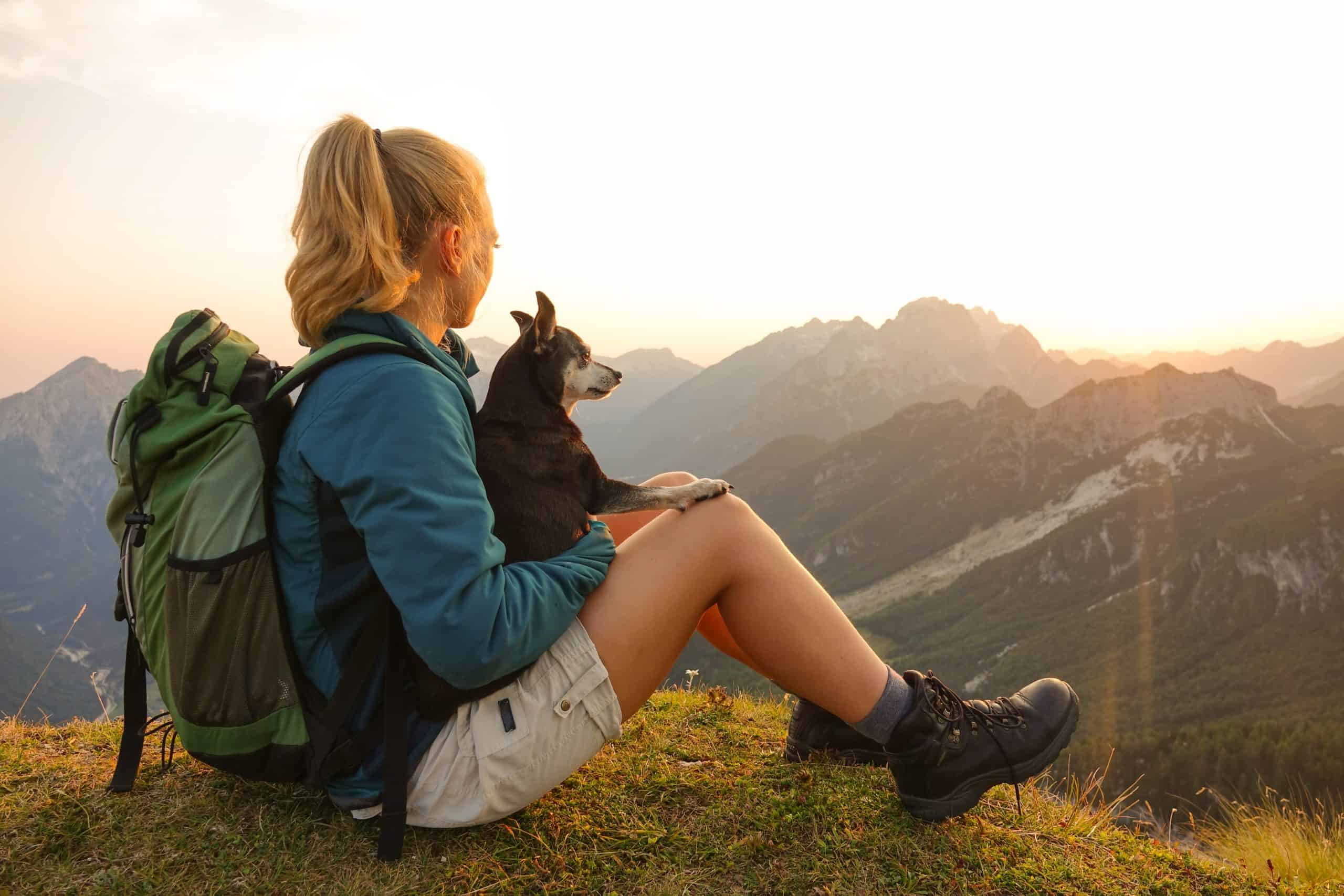 Woman on trekking adventure holds her small dog on her lap during a break. Trekking with dogs involves bringing their food and water, but how much? Walking for hours makes it necessary to increase the usual amount of water and food.