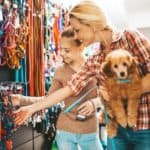 Mom and daughter buy supplies for pet poodle. Buying pet insurance could end up being a good way to save money on medical supplies and medications down the road.