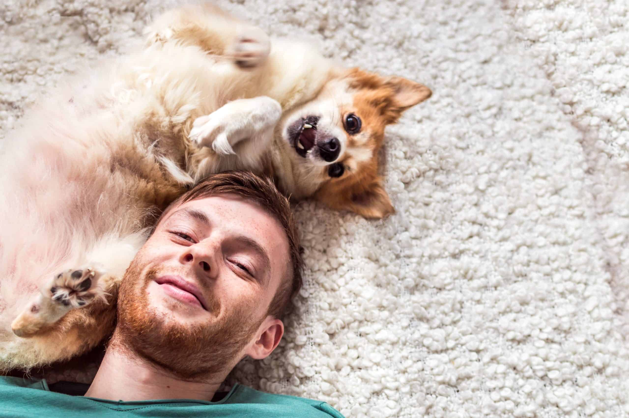 Man cuddles with puppy while lying on the floor. As a first-time dog parent, it's your responsibility to look out for your dog's nutrition, health, and entertainment.