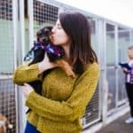 Woman kisses rescue dog at animal shelter.