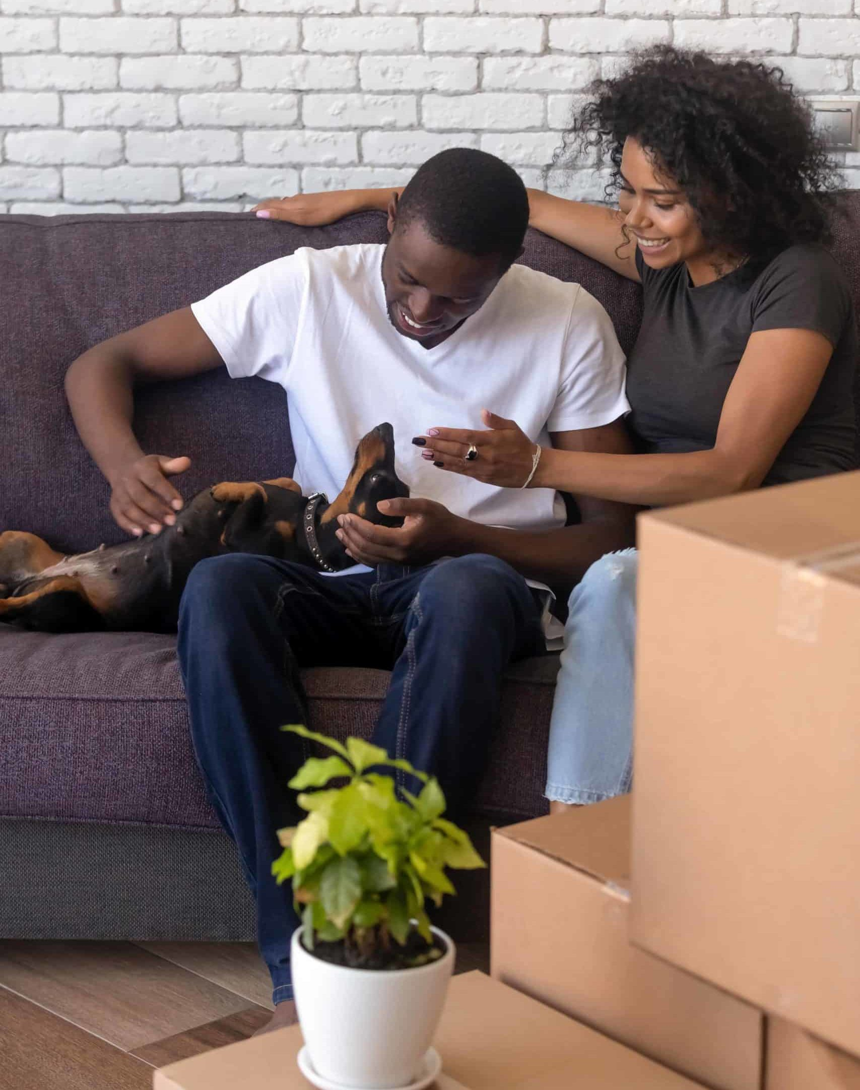 Couple sits on couch with Dachshund after moving. When renting, having all the rules explicitly stated is beneficial for all parties involved. This way, you will have a clear list of dos and don'ts before settling in with your pets.