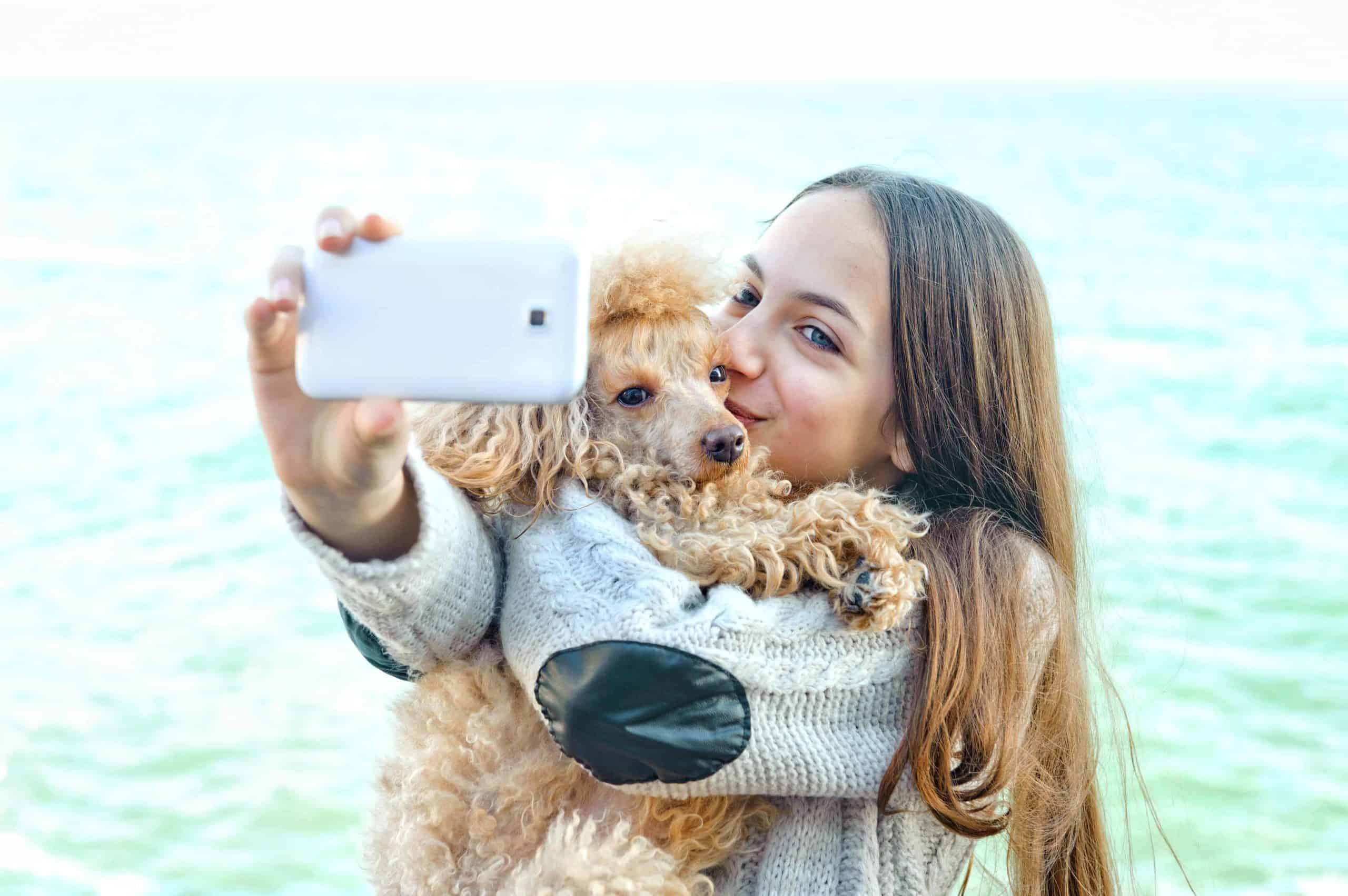 Owner takes selfie while holding her poodle. Creating a special social media account for your doggie is a way to share photos and videos of your pet without irritating your friends and family.