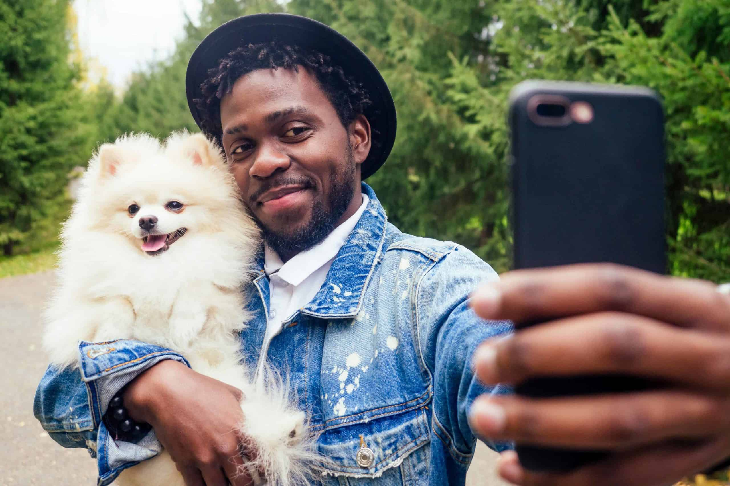 Owner takes selfie while holding his Spitz dog. Creating worthy social media content with animals is easier, as they all are cute and beautiful by default.