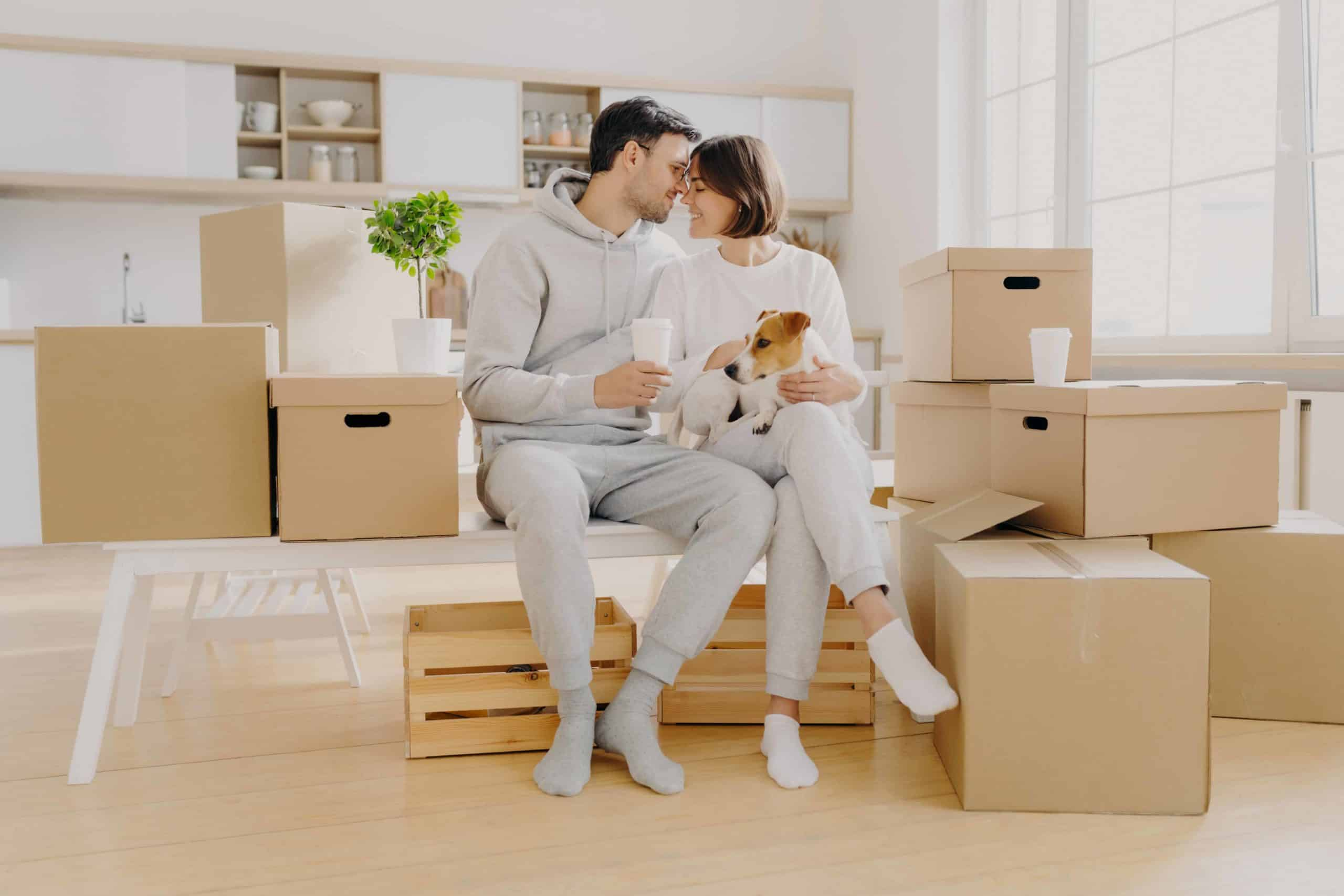 Couple sits with Jack Russell terrier while surrounded by moving boxes. If your landlord makes allowances for pets, do your part to keep your rental neat and free of destruction.