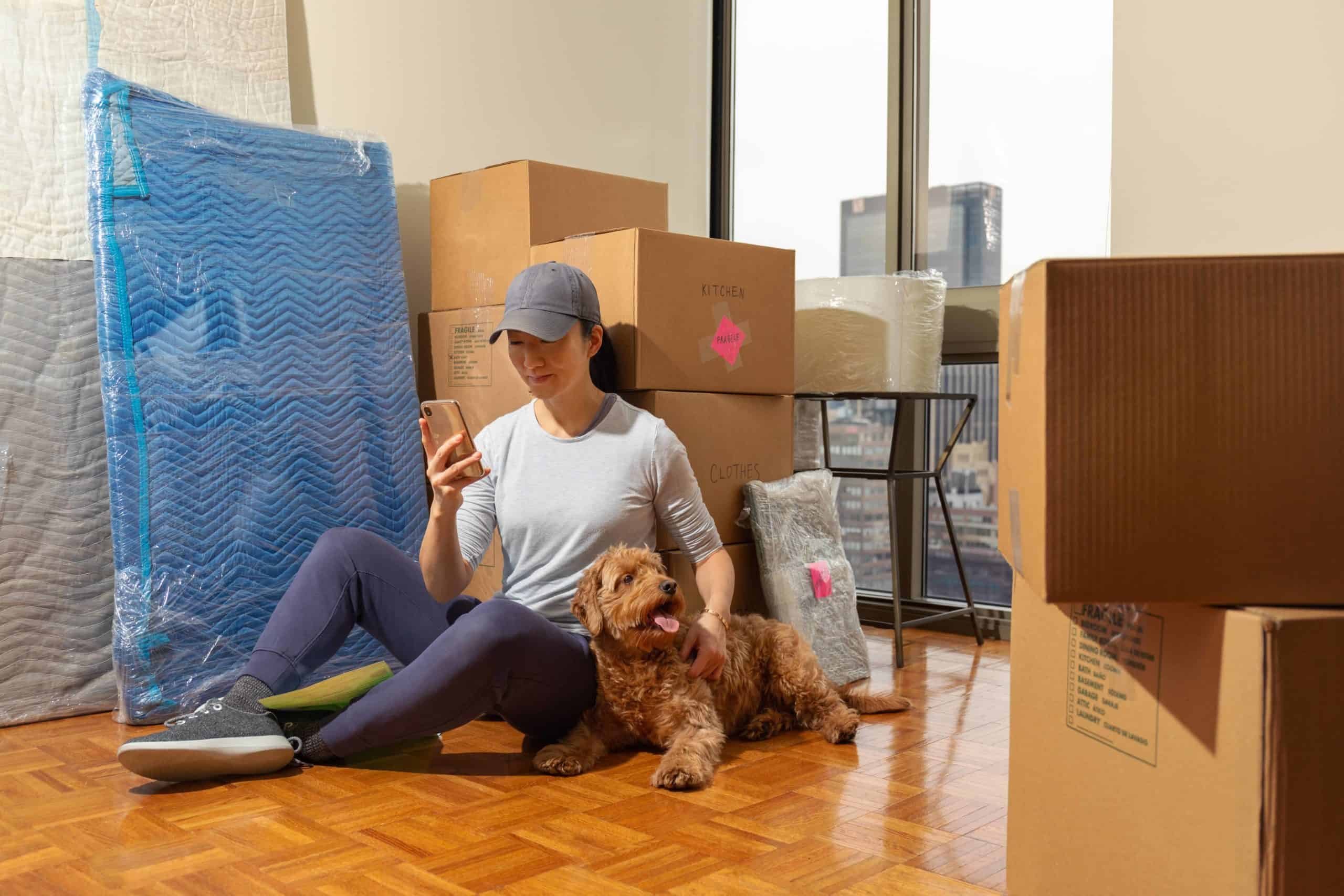 Woman relaxes with her goldendoodle after moving into a new apartment. Focus on 10 red flags to avoid when renting with pets. Follow your landlord's rules, train your dog, provide toys, and limit the time alone.