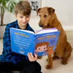 Boy reads book to dog. Scientific studies explore the advantages of bringing up children and dogs together and how it can be mutually beneficial.
