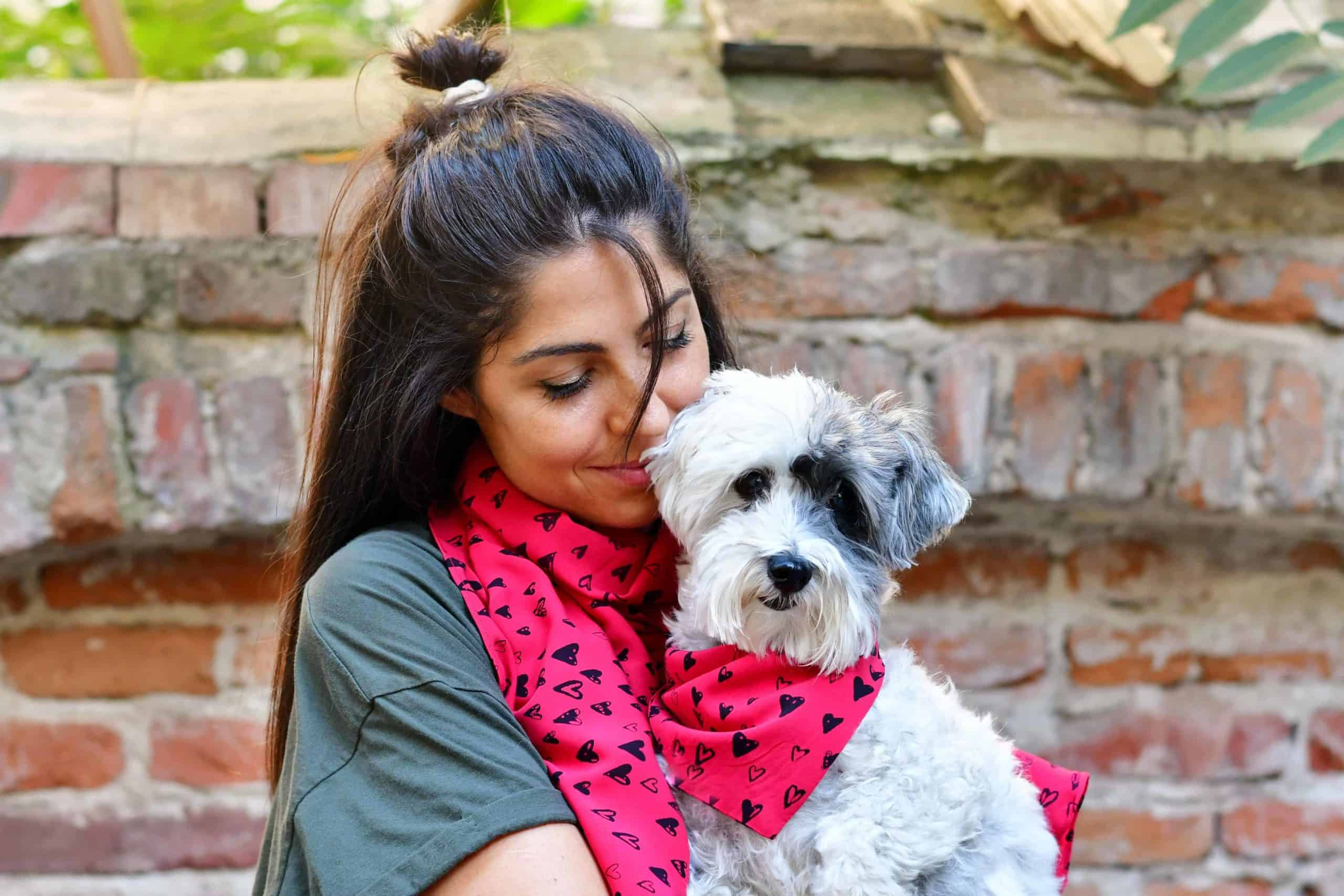 Woman wears scarf that matches her dog's bandana. Choose among perfect gift ideas for pet parents: automated toys, matching outfits, custom portraits, or custom collars and leashes.